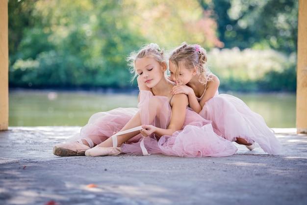 Twee schattige kleine ballerina's in roze jurken in de zomer buiten