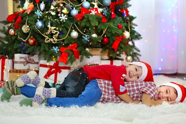 Twee schattige kleine broers liggen op tapijt op de decoratieachtergrond van kerstmis