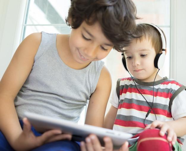 Twee schattige kleine broers met tablet thuis