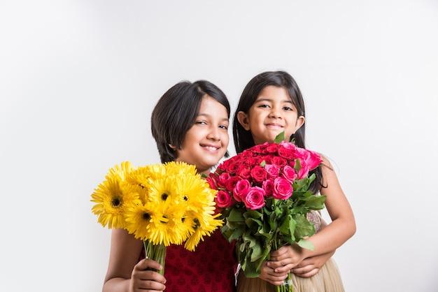 Twee schattige kleine indiase meisjes met een bos of boeket verse rode rozen of gulab-bloemen. geïsoleerd op witte achtergrond