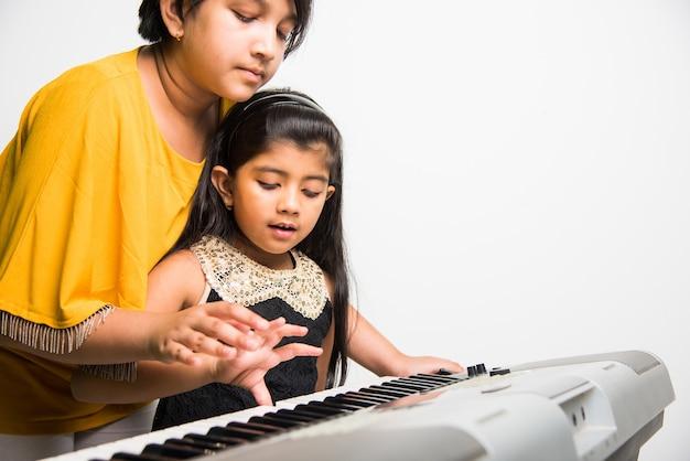 Twee schattige kleine indiase of aziatische meisjes spelen piano of keyboard, een muziekinstrument, op witte achtergrond