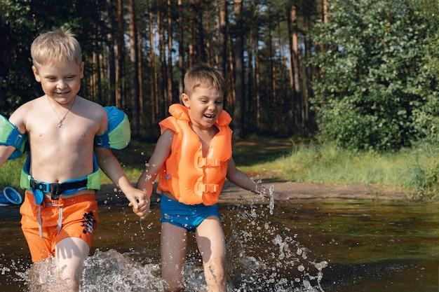 Twee schattige kleine jongens die in het bos tegen het meer opspattend water aanlopen