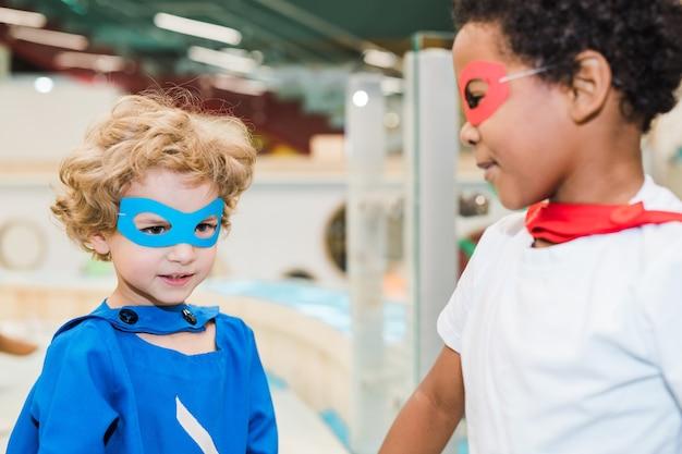 Twee schattige kleine jongens van verschillende etnische groepen dragen kostuums van superhelden die samen spelen in de kleuterschool