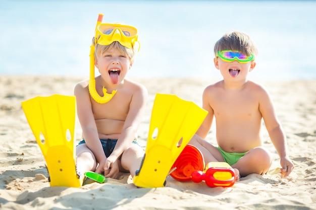 Twee schattige kleine kinderen spelen op het strand. jongens hebben plezier op de zomermuur. gelukkige kinderen.