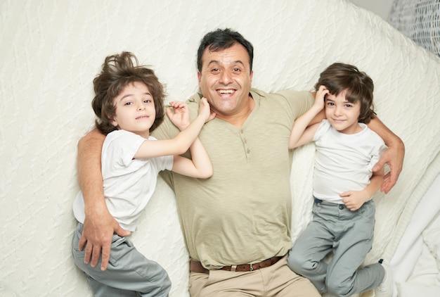 Twee schattige kleine latijns-jongens, kinderen en hun vader glimlachen naar de camera terwijl ze samen op een bed thuis liggen. gelukkige jeugd, ouderschapsconcept
