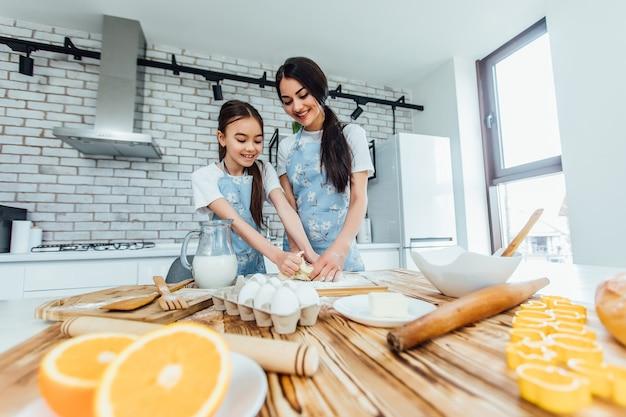 Twee schattige kleine meisjes die thuis koken