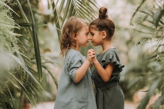 Twee schattige kleine meisjes die tot verschillende rassen behoren, hand in hand en wandelen in de botanische tuin