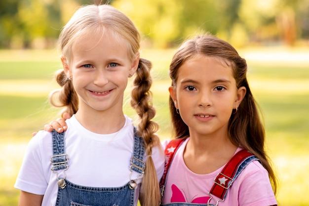 Twee schattige kleine meisjes glimlachen naar de camera