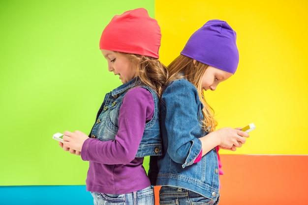 Twee schattige kleine meisjes met behulp van de telefoon