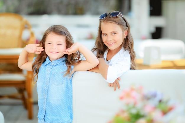 Twee schattige kleine meisjes permanent in jumpers en zonnebril op de achtergrond van het terras in de studio. zomer, plezier, familie en vakanties concept. twee modezusters poseren.