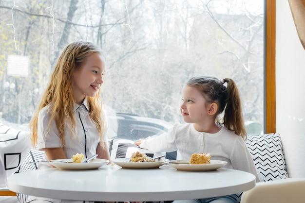 Twee schattige kleine meisjes zitten in een café en spelen op een zonnige dag. recreatie en levensstijl.