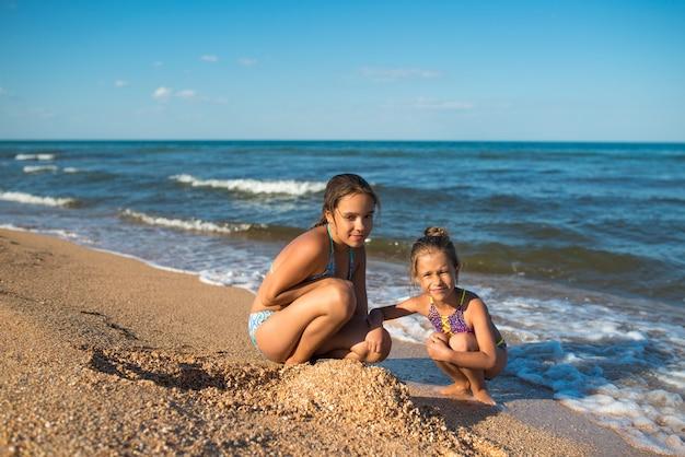 Twee schattige kleine zusjes spelen in het zand op het strand op een zonnige zomerdag. familie vakantie concept met kinderen. copyspace