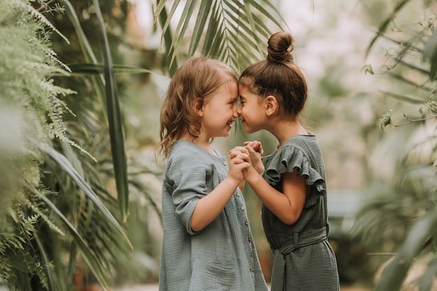 Twee schattige lachende kleine meisjes in linnen kleding hand in hand en wandelen in de botanische tuin