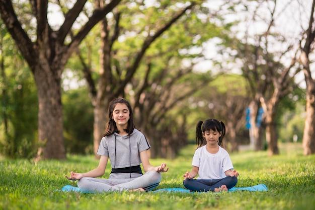 Twee schattige meisjes beoefenen van yoga in het park