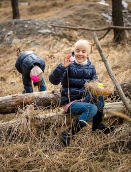 Twee schattige meisjes die paaseieren zoeken in het bos op koude aprildag