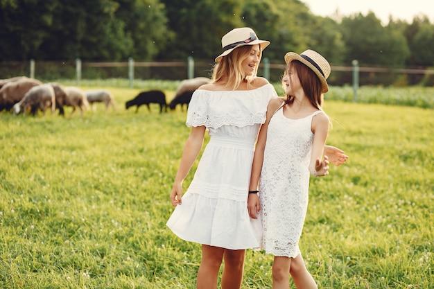 Twee schattige meisjes in een veld met een geit