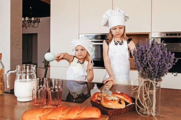 Twee schattige meisjes in koksmutsen en witte schorten koken in de keuken.