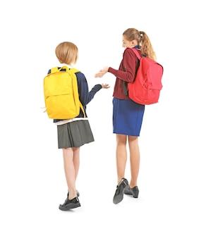 Twee schattige meisjes in schooluniform op wit