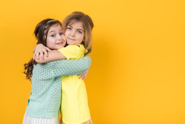 Twee schattige meisjes knuffelen