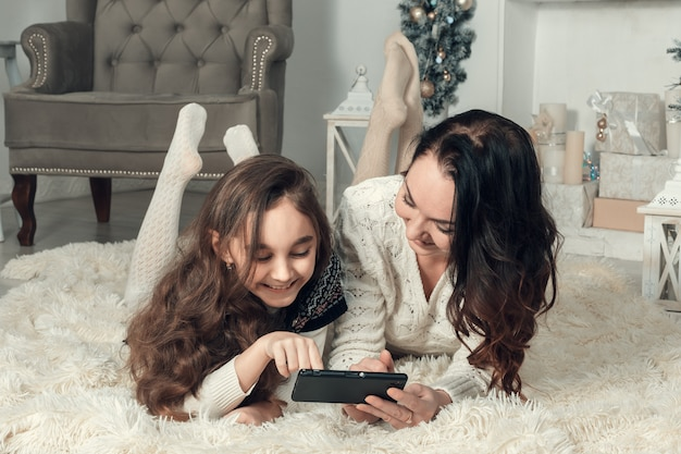 Twee schattige meisjes, moeder en dochter liggend op een vloer in kerstmis ingerichte kamer, gebruiken een mobiele telefoon.
