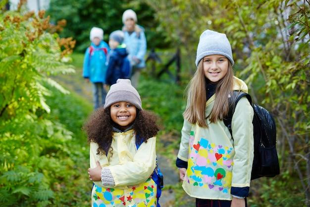Twee schattige meisjes op weg naar school in de herfst