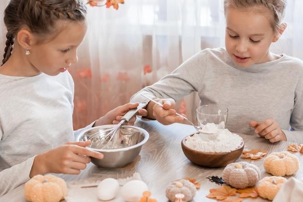Twee schattige meisjes slaan peperkoekdeeg om halloween-koekjes te maken in de thuiskeuken. traktaties en voorbereidingen voor het halloween-feest