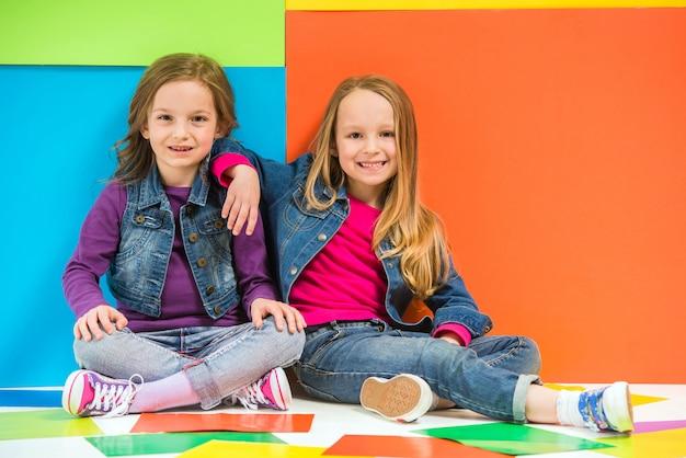 Twee schattige meisjes zittend op de vloer op kleurrijke muur