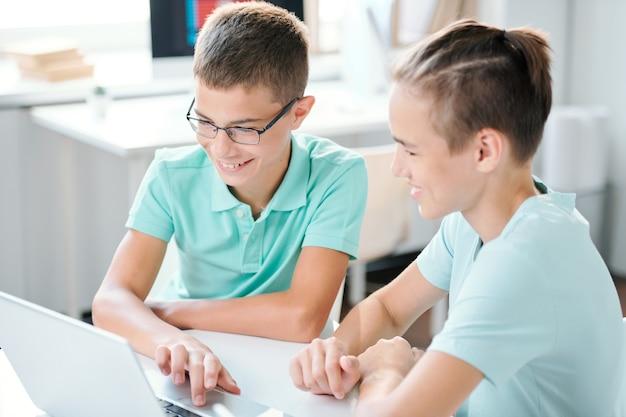 Twee schattige middelbare schooljongens die bij bureau voor laptopvertoning zitten en huistoewijzing voorbereiden