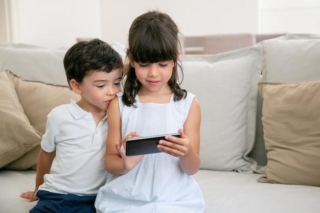 Twee schattige nieuwsgierige jongen en meisje zittend op de bank thuis en met behulp van smartphone.