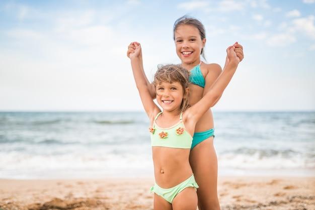 Twee schattige positieve kleine meisjeszusjes staken hun hand op tijdens het zwemmen op zee tijdens de vakantie op een warme zomerdag