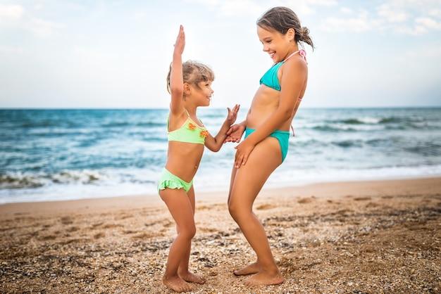 Twee schattige positieve zusjes meisjes staken hun handen omhoog tijdens het zwemmen op zee tijdens de vakantie op een warme zomerdag.