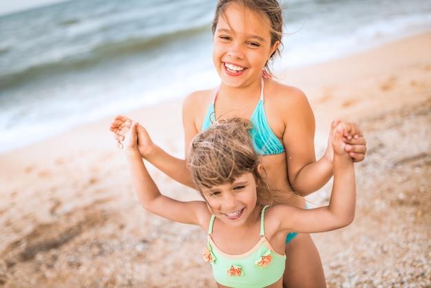 Twee schattige positieve zusjes staken hun hand op
