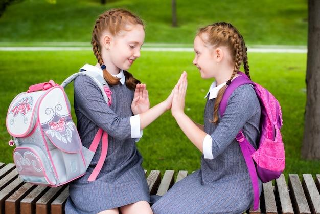 Twee schattige schoolmeisjes zitten op een bankje en glimlachen. houden zich vast aan de rode staartjes. de zusjes gaan graag weer naar school. roodharigen