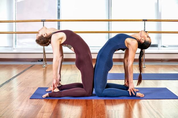 Twee schattige slanke jonge vrouwen doen de yoga pose terwijl ze in een lichte sportschool in de buurt van een groot raam staan. concept basisyoga-oefeningen en groepslessen