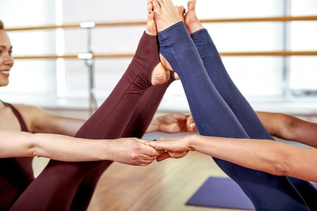 Twee schattige slanke jonge vrouwen doen de yogahoudingen