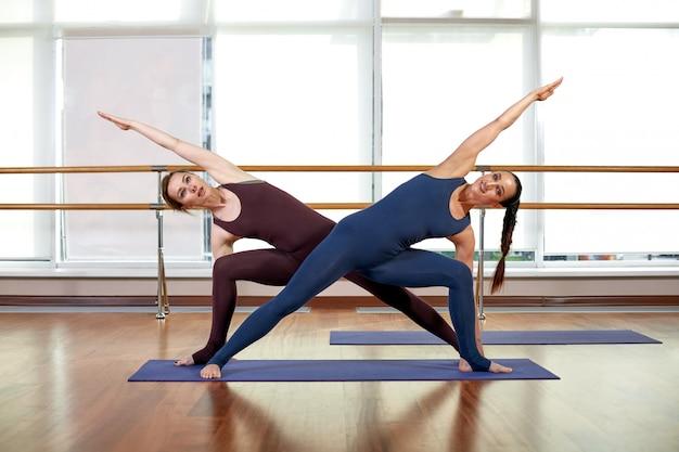Twee schattige slanke jonge vrouwen doen de yogapose