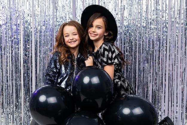 Twee schattige stijlvolle jonge meisjes in vakantie jurken met zwarte ballonnen op een glanzende muur
