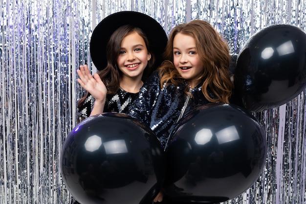 Twee schattige stijlvolle jonge zusters in vakantie jurken met zwarte ballonnen op een feestje op een glanzende muur