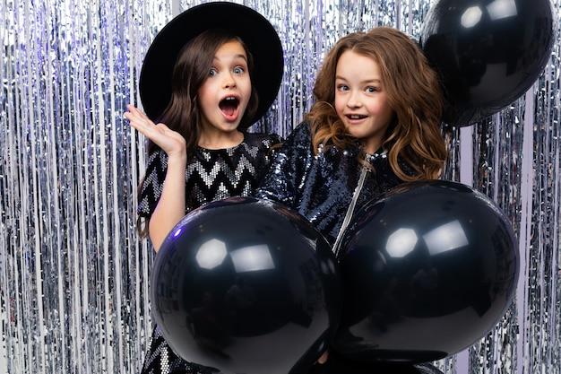 Twee schattige stijlvolle jonge zusters in vakantie jurken met zwarte ballonnen op een glanzende muur