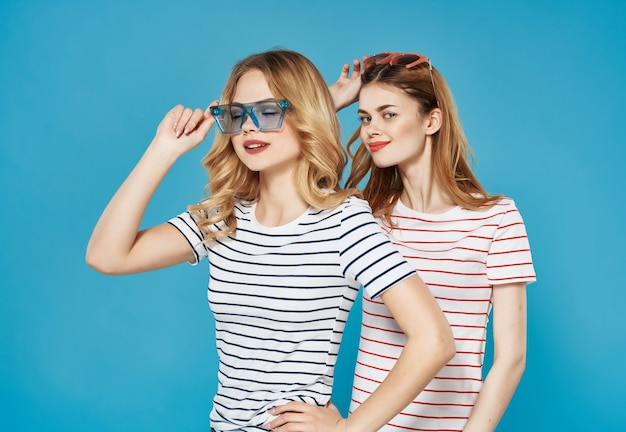 Twee schattige vriendinnen zomer mode plezier knuffel blauwe achtergrond