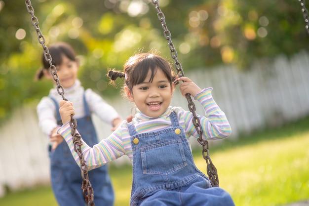Twee schattige zusjes die samen plezier hebben op een schommel in een mooie zomertuin op een warme en zonnige dag in de buitenlucht. actieve zomerrecreatie voor kinderen.