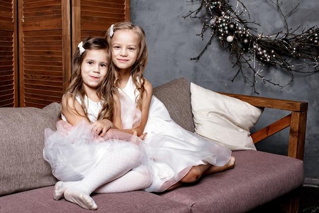 Twee schattige zusjes in witte jurken, zittend op de bank dicht bij elkaar en thuis spelen. zusje knuffelt haar kleinste zusje.