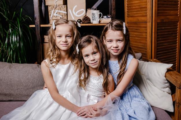 Twee schattige zusjes in witte jurken, zittend op de bank dicht bij elkaar en thuis spelen.