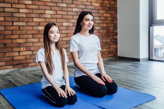 Twee schattige zussen die samen yoga beoefenen in het yogacentrum.