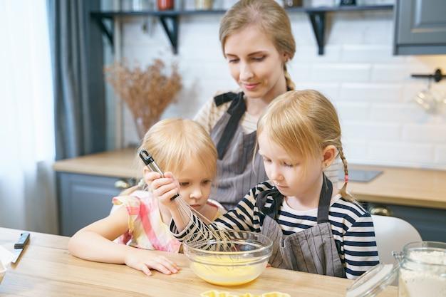 Twee schattige zussen helpen moeder in de keuken. gelukkige familie die deeg voor koekjes voorbereidt