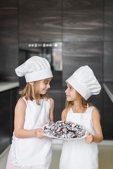 Twee schattige zussen kijken elkaar gebakken koekjes te houden