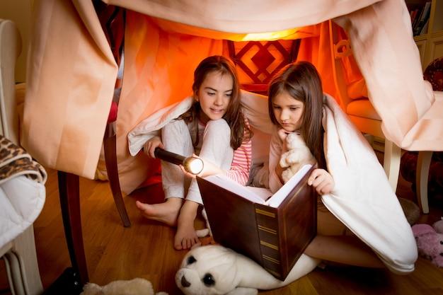 Twee schattige zussen zitten in huis gemaakt van dekens en leesboek