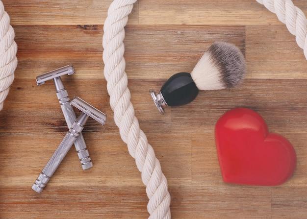Twee scheermessen, borstel, hart en touw op een houten achtergrond