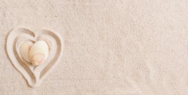 Twee schelpen in de vorm van een hart op een gladde zandstrand met kopie ruimte, bovenaanzicht