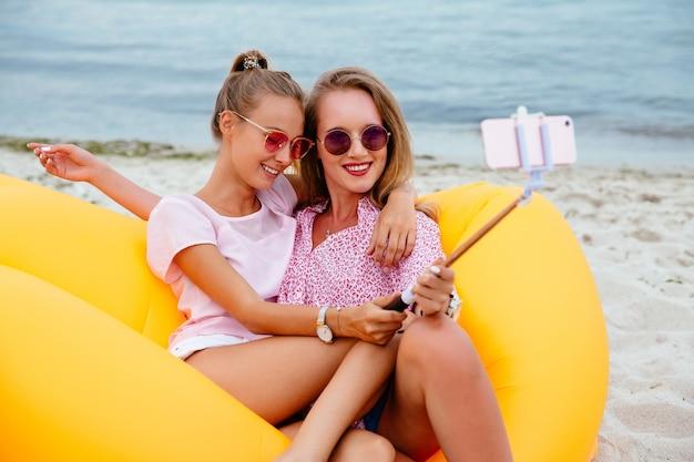 Twee schitterende glimlachende meisjes in zonnebril die een foto op selfiestok nemen